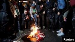 Pasca terpilihnya Donald Trump, beberapa warga AS melakukan protes di luar Trump Tower di New York, dengan membakar bendera Amerika, hari Rabu (9/11).