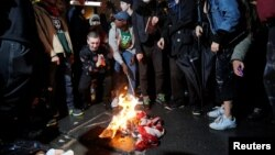 Following President-elect Donald Trump's election victory, protesters burn a U.S. flag outside Trump Tower in New York, Nov. 9, 2016.