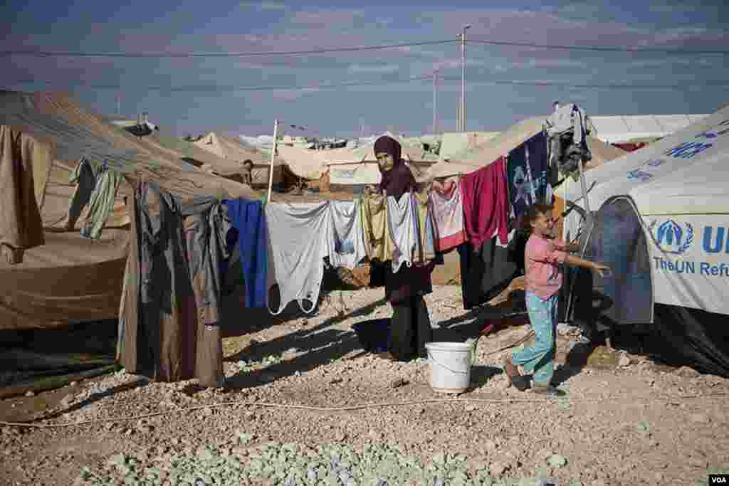 A woman hangs clothes to dry at the Za'tari refugee camp. (Y. Weeks/VOA)