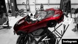 """Starman"" sits behind the wheel of a Tesla roadster in this photo posted to the Instagram account of Elon Musk, head of the Tesla car company and founder of SpaceX."