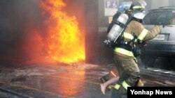 10일 불이 난 아파트에서 소방대원들이 주민들을 구조하고 있다.