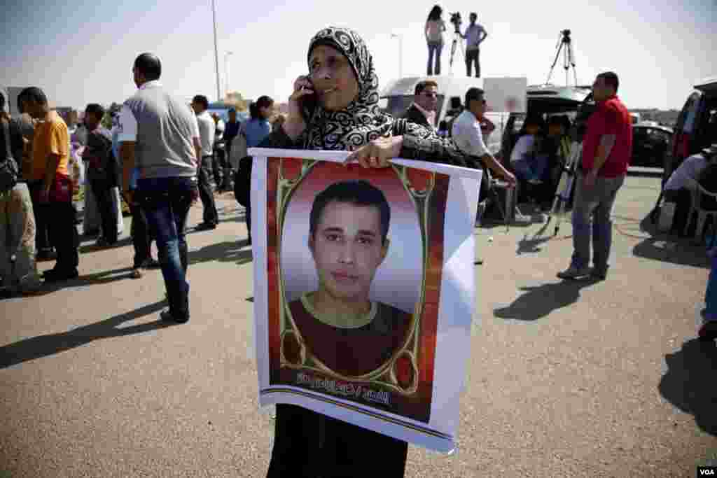 A woman holds a sign with the image of a slain protester in front of a courthouse in Cairo awaiting a verdict in the trial of former Egyptian president Hosni Mubarak, June 2, 2012. (VOA/Y. Weeks)