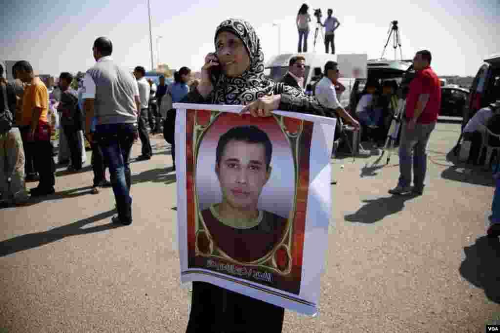 Một phụ nữ cầm hình ảnh của một người biểu tình bị giết chết ở phía trước tòa án xét xử ông Mubarak ở Cairo
