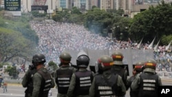 FILE - Bolivarian National Guards stand on a highway overlooking an anti-government march trying to make its way to the National Assembly in Caracas, Venezuela, May 3, 2017.