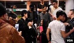 集會進行期間有懷疑親北京人士(手持粉紅手機者)在場拍攝,被集會人士包圍,由港大保安人員護送離場。(美國之音湯惠芸)