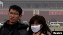 A woman wears a mask as she visits Tiananmen Square in Beijing, Jan. 13, 2013.