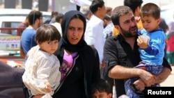 Keluarga Irak meninggalkan kota Mosul setelah kota ini jatuh ke tangan pemberontak Irak (10/6).