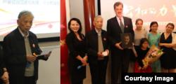 """左图:重病康复中的""""中国法律界良知""""张思之致颁奖辞。右图:2014年度公和人物颁奖典礼会主持人耿潇男女士(左一)与她称为""""圣徒""""而鼎力推荐的卢百可先生,与张思之先生(左二)共同为卢百可颁奖。(左三)卢百可带他的四个女儿与颁奖人在颁奖台合影,手持木刻画像由独立学人毛喻源雕刻(耿潇男拍摄)"""