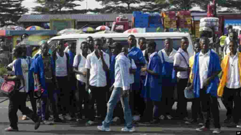 Une scène de gnes qui attendent un moyen de transport à Kinshasa. Une partie importante du transport est assurée par les conducteurs des taxi-motos accusés d'être des membres des gangs que la police a visés. (AP Photo/Saul Loeb, Pool)