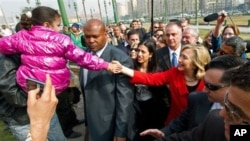 US Secretary of State Hillary Clinton shakes hands with a child as she takes an unannounced walk through Tahrir Square, in Cairo, Egypt, March 16, 2011