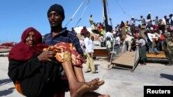 Un homme porte une vieille femme qui a débarqué d'un bateau transportant des déplacés qui fuient les violences au Yémen, au port de Bosaaso dans la région somalienne de Puntland, jeudi 16 avril 2015.