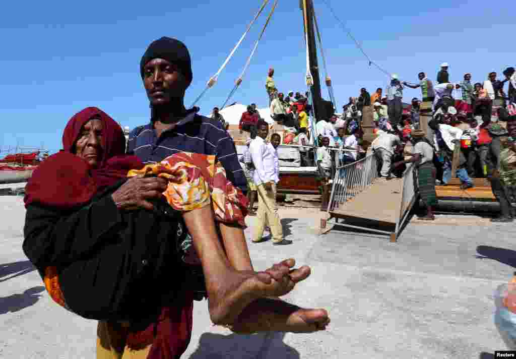 A man carries an elderly woman from a ship carrying people fleeing violence in Yemen, at the port of Bosasso in the Puntland region.