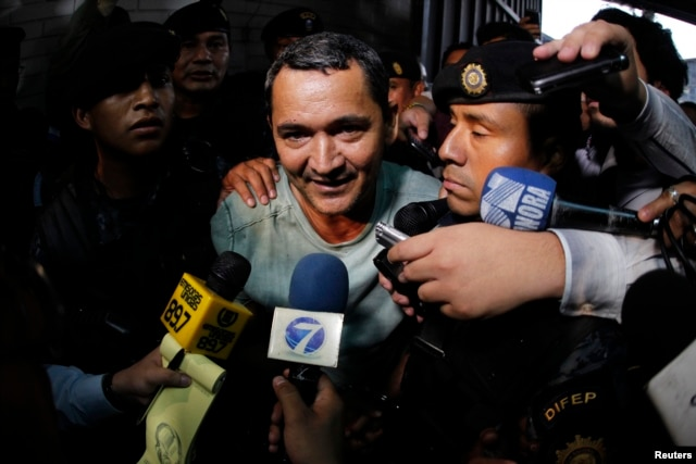 FILE - Waldemar Lorenzana (C) speaks with members of the media after his arrest at the Supreme Court of Justice in Guatemala City, Sept. 17, 2013.