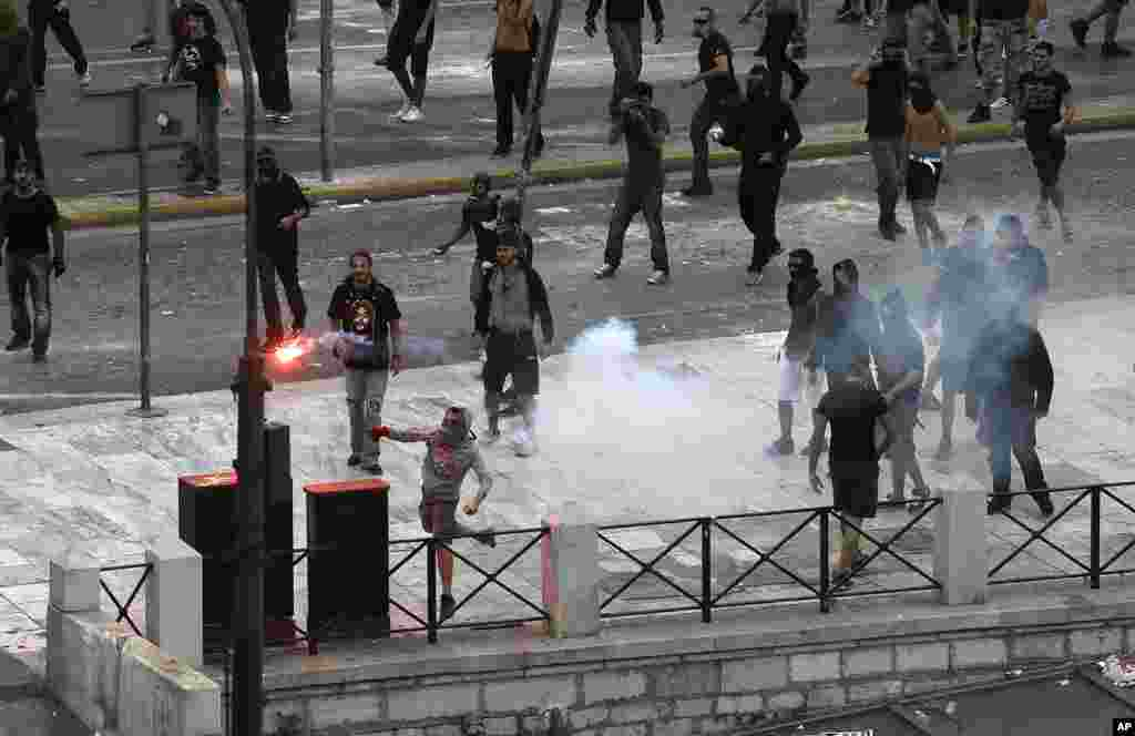 A protester throws a flare towards riot police during clashes during a protest in Athens, Greece, October 9, 2012.