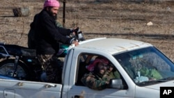 A group of unidentified militants drive near Syria's Quneitra border crossing between Syria and the Israeli-controlled Golan Heights, seen from the Israeli-controlled Golan Heights, Nov. 28, 2016. Israeli aircraft struck a machine gun-mounted vehicle inside Syria Nov. 27, killing four IS-affiliated militants inside after they had opened fire on a military patrol on the Israeli side of the Golan Heights, the Israeli military said.
