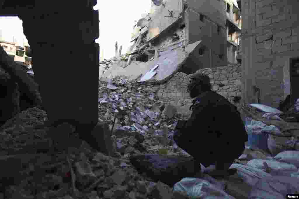 A Free Syrian Army fighter sits amid the rubble of damaged buildings in Deir al-Zor, eastern Syria, Feb. 6, 2014.