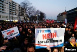FILE - Protesters carry banners reading 'No refugee home' during an Austrian Freedom Party (FPOe) demonstration in Vienna, March 14, 2016.