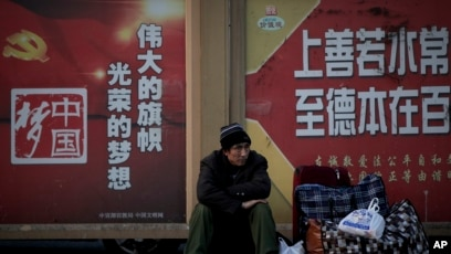 A migrant worker sits next to his belonging against a wall displaying a Chinese government propaganda message at the Beijing railway station in Beijing, Monday, Jan. 21, 2019.