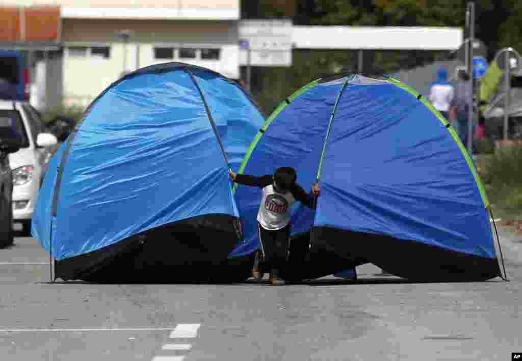 """A migrant boy pulls tents on the road near the """"Horgos 2"""" border crossing into the Hungary, near Horgos."""