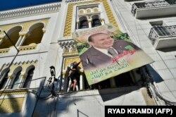 Bouteflika'nın posterini indirmeye çalışan bir Cezayirli gösterici