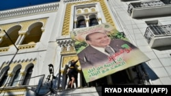 အယ္လ္ဂ်ီးရီးယား သမၼတ Abdelaziz Bouteflika ရဲ႕ ရုပ္ပံုကို ဆႏၵျပသူမ်ားက ျဖဳတ္ခ်ေနစဥ္