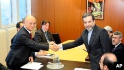 Deputi Menlu Iran, Abbas Araghchi (kanan) berjabat tangan dengan Direktur IAEA, Yukiya Amano di Wina hari Senin (28/10).