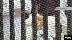 Mantan Presiden Hosni Mubarak terbaring di tempat tidur di dalam kurungan yang dibangun di depan ruang pengadilan (3/8).
