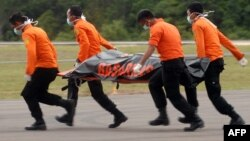 Members of an Indonesian search and rescue team carry a dead body with a stretcher during the recovery of victims who were onboard the crashed AirAsia flight QZ8501 in Pangkalan Bun on December 31, 2014. Stormy weather forced Indonesian rescuers on Decemb