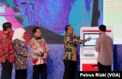 Seorang warga mencoba mesin Anjungan Dukcapil Mandiri untuk mencetak Kartu Keluarga (Foto:VOA/ Petrus Riski).