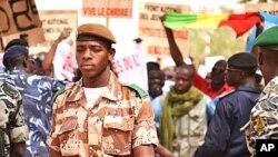 Mwanajeshi akitembea na baadhi ya waandamanaji kwenye uwanja wa ndege wa bamako nchini Mali, Machi 29, 2012
