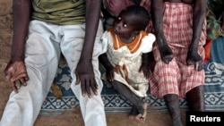 FILE - A girl sits between her leprosy-afflicted parents. A leprosy isolation camp in Bor County's Malek village, located in South Sudan's Jonglei state, has just received aid supplies for the first time in two years.