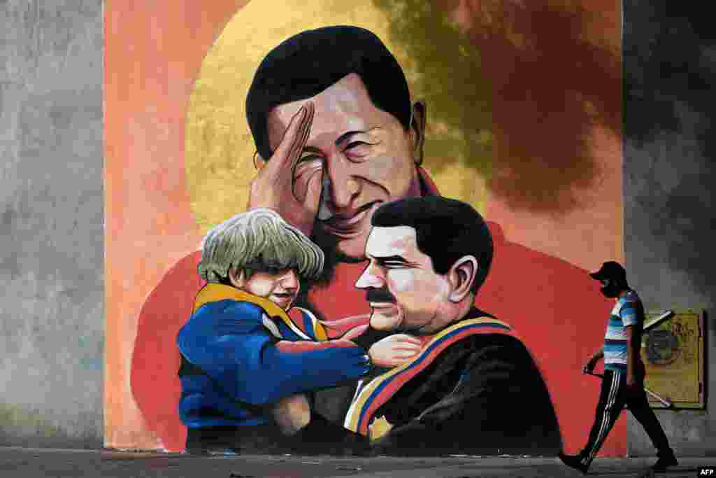 A man walks past artwork showing the late Venezuelan President Hugo Chavez saluting and Venezuelan President Nicolas Maduro, right, holding a child in Caracas.