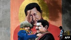Một người đi ngang qua tranh tường vẽ cố TT Hugo Chavez, giữa, giơ tay chào TT Nicolas Maduro, phải, đang bồng một đừa trẻ ở Caracas. (Photo by Federico PARRA / AFP)