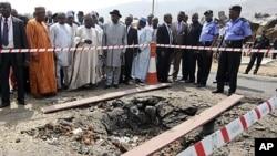 Le président Goodluck Jonathan (au c. avec le chapeau noir) visite l'église Sainte Thérèse, près d'Abuja, qui a été attaquée le jour de Noël (31 déc. 2011)