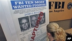 FBI Special Agent Mary Prang sets up a 'wanted' poster overstamped 'captured' for James 'Whitey' Bulger, before a news conference at FBI headquarters in Los Angeles, June 23, 2011