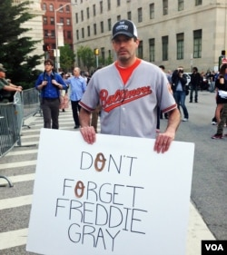 A demonstrator, wearing the uniform of the Orioles baseball team on the street in Baltimore. (VOA photo - Victoria Macchi).