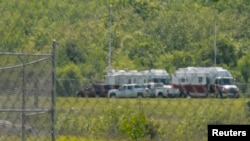 Emergency trucks and crew surround the crash scene off the runway at Hanscom Field in Bedford, Massachusetts, Sunday June 1, 2014.