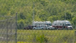 Emergency trucks and crew surround the crash scene off the runway at Hanscom Field in Bedford, Massachusetts, Sunday June 1, 2014.