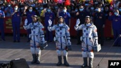 Astronauts Nie Haisheng (R), Liu Boming (C) and Tang Hongbo wave during a departure ceremony before boarding the Shenzhou-12 spacecraft before lift off on a Long March-2F carrier rocket at the Jiuquan Satellite Launch Centre in the Gobi desert in northwest China on June 17, 2021.