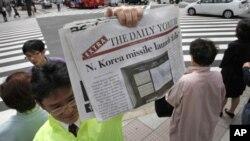 Một nhân viên của nhật báo Yomiuri của Nhật Bản cầm tờ báo đăng tin hàng đầu về vụ phóng tên lửa thất bại của Bắc Triều Tiên