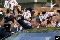 Tổng thống Hàn Quốc Moon Jae-in vẫy chào người dân tụ tập gần Dinh Ngói Xanh (phủ tổng thống) trước khi lên đường đến dự hội nghị thượng đỉnh liên Triều, Seoul, Hàn Quốc, ngày 27 tháng 4, 2018.