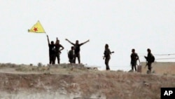 Fighters with the Kurdish People's Protection Units, or YPG, wave their yellow triangular flag on the outskirts of Tal Abyad, Syria, June 15, 2015.