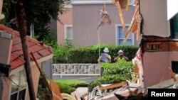 Inspectores continuán revisando las áreas destruidas al ser absorvidas por el socavón en el hotel turístico Summer Bay Resort.