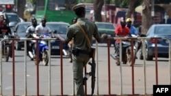 L'officier de police burkinabé monte la garde devant une porte lors de la dernière étape du Tour du Faso 2018, à Ouagadougou, le 4 novembre 2018.