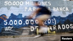 A man rides his bicycle past graffiti that says '50,000 million for rescuing banks and five million unemployed' in Burgos, central Spain, June 28, 2012.