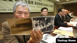 24일 서울 프레스센터에서 열린 '일본 전범기업 상대 손해배상 청구소송 기자회견'에서 손일석 소송회장(왼쪽)이 강제동원의 실상을 담은 사진자료를 공개하고 있다.
