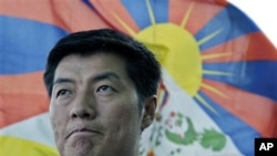 FILE- In this March 20, 2011 file photo, Tibetan prime ministerial candiadate Lobsang Sengey, gestures as he talks to the Associated Press in the backdrop of a Tibetan flag in Dharmsala, India. Legal expert Sangay has won the election to become head of th