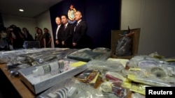 Officers from Police Organized Crime and Triad Bureau (L-R) Chief Inspector Tsue Chun-tung, Chief Superintendent Au Chin-chau and Superintendent Ng Wai-hon, in front of items relating to making explosives seized, at police headquarters in Hong Kong, June 15, 2015.