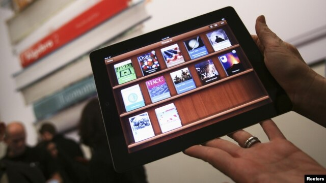A woman holds up an iPad with the iTunes U app after a news conference introducing a digital textbook service, in New York, January 2012. (file photo)