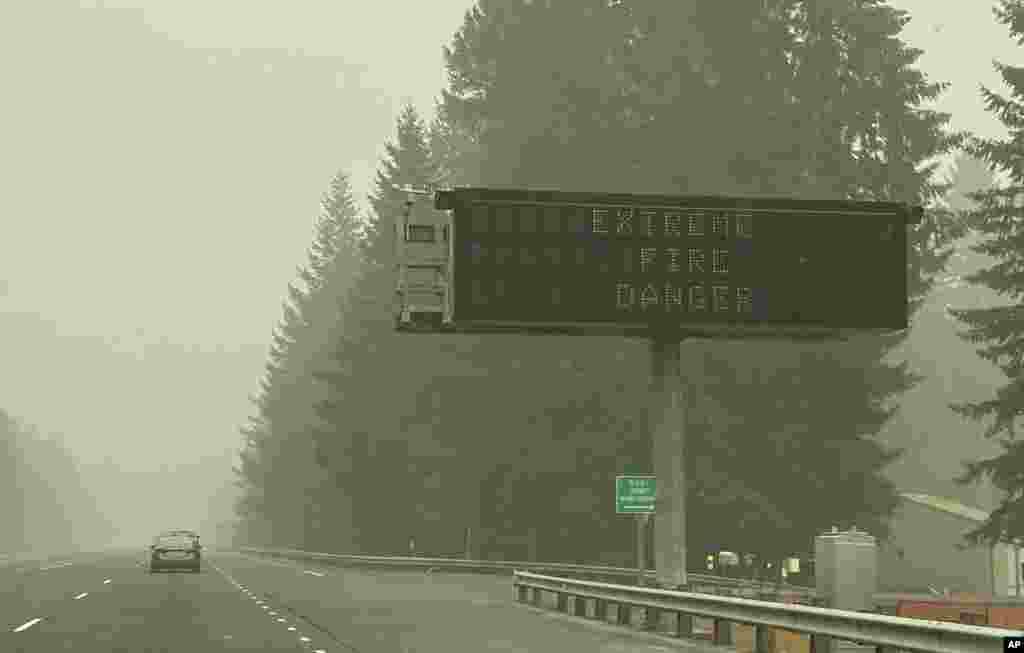 ផ្លាកសញ្ញាបង្ហាញអំពីគ្រោះថ្នាក់នៃភ្លើងឆេះព្រៃ ត្រូវបានដាក់នៅលើផ្លូវជាតិមួយ នៅទីក្រុង Sandy ដែលគ្របដណ្តប់ដោយផ្សែង ក្នុងរដ្ឋ Oregon កាលពីថ្ងៃទី ១៤ ខែកញ្ញា ឆ្នាំ ២០២០។